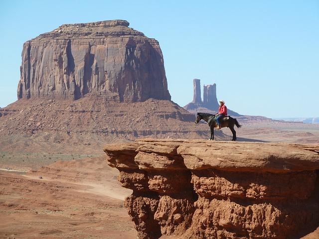 Cowboy auf einem Pferd mitten im Monument Valley.